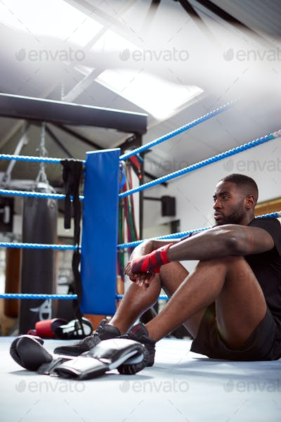 Tired Male Boxer Sitting In Boxing Ring In Gym After Training Session