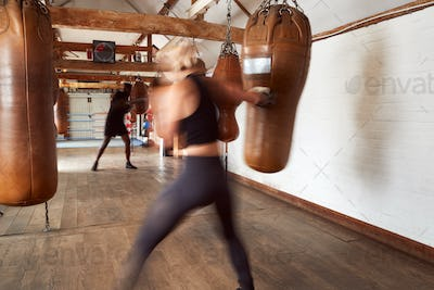 Action Shot Of Male And Female Boxers In Gym Training With Leather Punch Bags