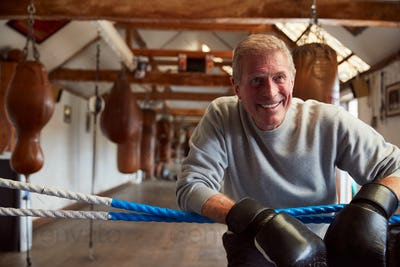 Smiling Senior Male Boxer In Gym Wearing Boxing Gloves Leaning On Ropes Of Boxing Ring