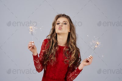 Beautiful woman with burning sparklers blowing a kiss