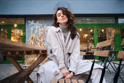 Gorgeous stylish brunette girl in trench coat sensually posing on camera in cafe on city street
