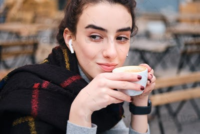 Pretty brunette girl with wireless earphones drinking coffee while wistfully looking away outdoor