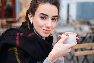 Pretty girl with wireless earphones happily looking in camera drinking coffee in cafe outdoor