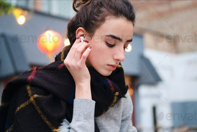 Portrait of pensive brunette girl listening music in wireless earphones