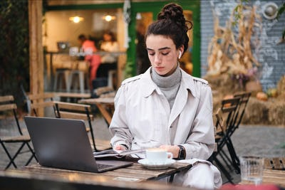 Beautiful casual brunette girl in trench coat with coffee studying on laptop in cafe on city street