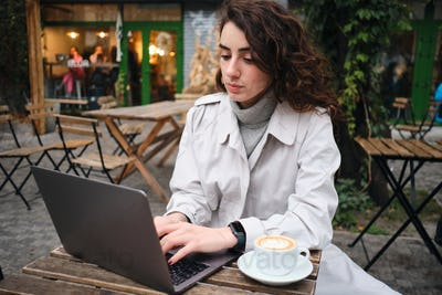 Attractive casual girl in trench coat confidently studying on laptop with coffee in cafe outdoor