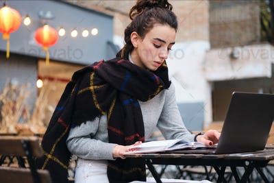 Concentrated girl with scarf thoughtfully reading book studying with laptop in cafe on city street