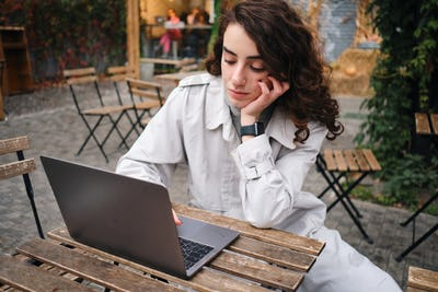 Beautiful casual girl in trench coat thoughtfully working on laptop in cafe outdoor