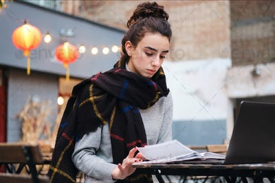Concentrated brunette girl with scarf reading book studying with laptop in cafe on city street