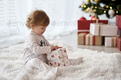 Side view of charming baby opening Christmas gift