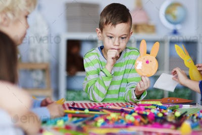 Focused boy with handmade decoration for Easter