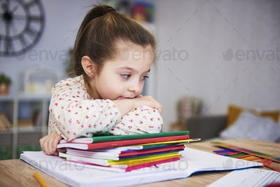Tired and bored student with stack of books