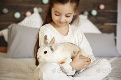 Close up of girl embracing fluffy rabbit