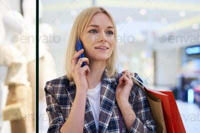 Young woman with full shopping bags talking by mobile phone