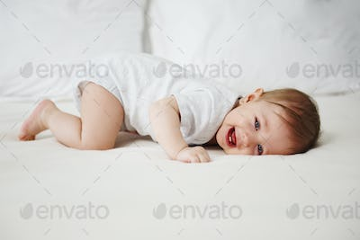 Playful baby having fun in bed