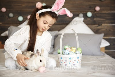 Girl playing with rabbit in bedroom