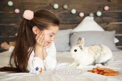 Cheerful girl looking at rabbit