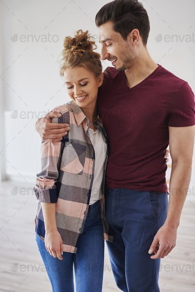 Happy couple embracing in their new home