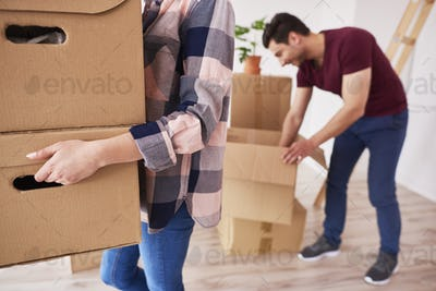 Part of woman carrying cardboard boxes into new apartment
