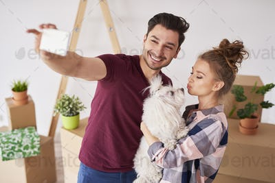 Happy couple with dog making a selfie in new home