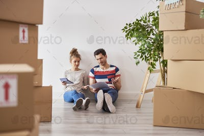 Worried couple examining expenses next to moving boxes