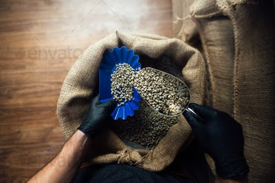 pouring coffee from a burlap bag into a bowl for tasting