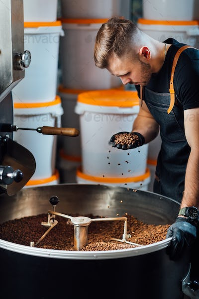 A worker near coffee roasting equipment will check time for testing the sample.