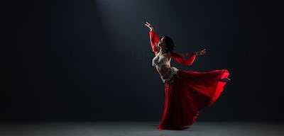 Woman in red arabic dress dancing oriental dances arabesque pose