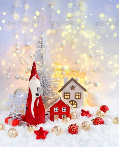 Christmas composition with the gnome, decorative huts and festive decorations оn the snow