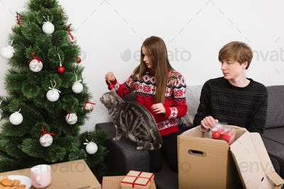 Pretty young couple sitting on sofa at home decorating Christmas tree together with cute cat near