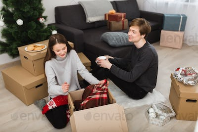 Girl dreamily opening box sitting with boy holding mug on floor at home near Christmas tree