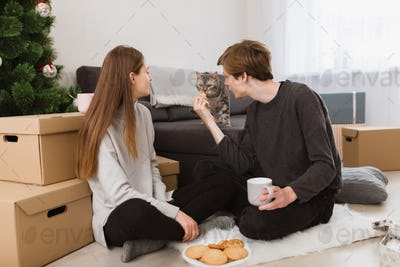 Portrait of young beautiful couple sitting on floor at home with cookies and looking at cat near