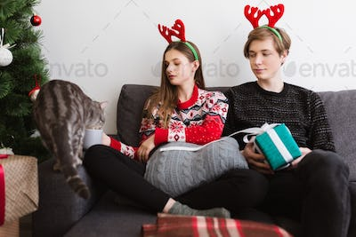 Portrait of young beautiful couple sitting on sofa at home and wearing deer horns with cat near