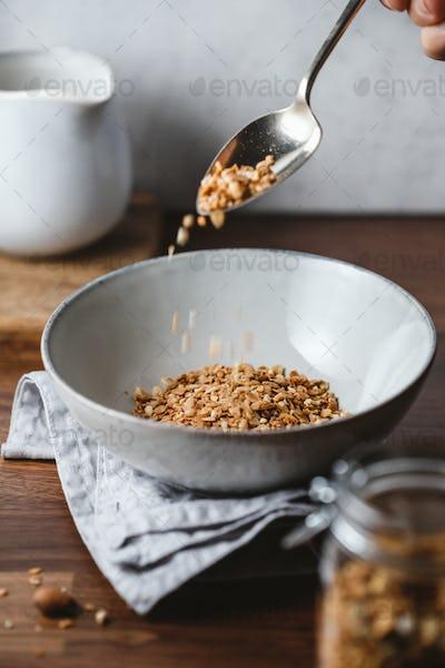 Hand sprinkles baked granola in a ceramic bowl