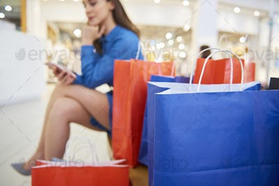 Shopping bags and woman with mobile phone in the background