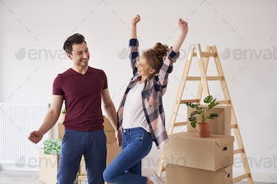 Cheerful couple having fun in their new apartment