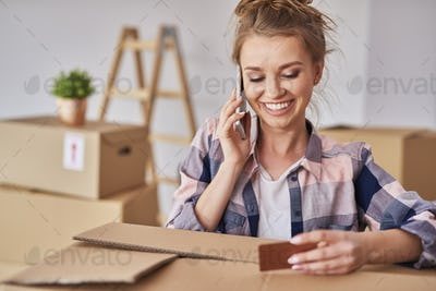 Smiling woman using phone while moving house