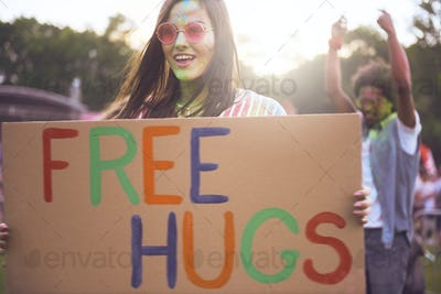 """Happy woman holding banner """"free hugs"""" during summer music festival"""
