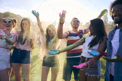 Friends having fun during music festival with colour powders