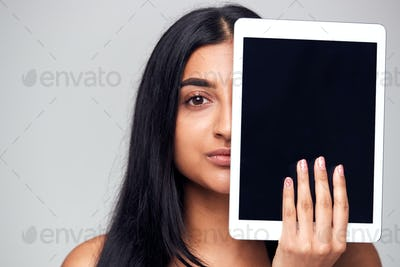 Studio Portrait Of Serious Young Woman Covering Face With Digital Tablet