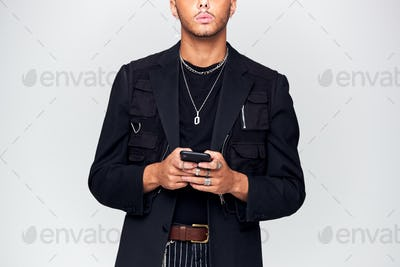 Close Up Studio Shot Of Causally Dressed Young Man Using Mobile Phone