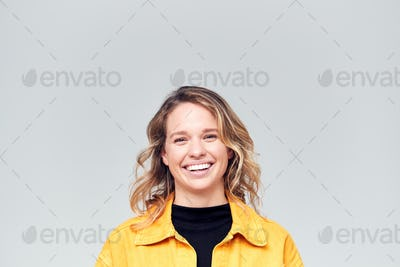 Studio Portrait Of Positive Happy Young Woman Smiling At Camera