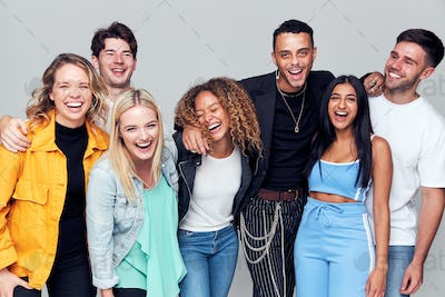 Group Studio Shot Of Young Multi-Cultural Friends Smiling And Laughing At Camera