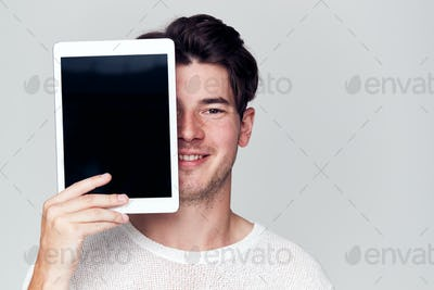 Studio Portrait Of Smiling Young Man Covering Face With Digital Tablet