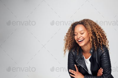 Studio Shot Of Happy Young Woman With Folded Arms Wearing Leather Jacket Laughing Off Camera