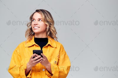 Studio Shot Of Causally Dressed Young Woman Using Mobile Phone Looking Off Camera
