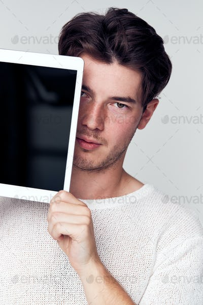 Studio Portrait Of Worried Young Man Covering Face With Digital Tablet