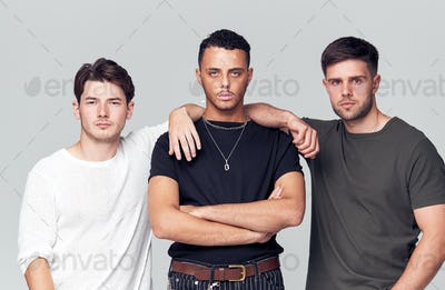 Group Studio Portrait Of Multi-Cultural Male Friends Looking Into Camera With Serious Expression