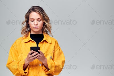 Studio Shot Of Causally Dressed Young Woman Using Mobile Phone