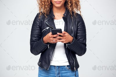 Close Up Studio Shot Of Woman Wearing Leather Jacket Using Mobile Phone